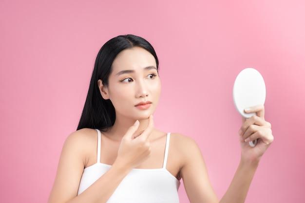 Azjatycka kobieta patrząc w lustro i martwiąc się o swoją skórę.
