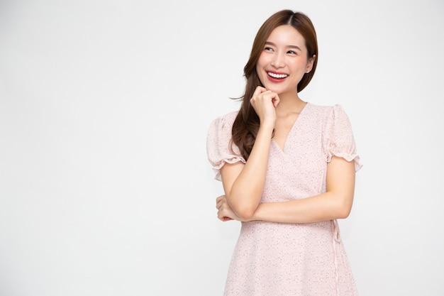 Azjatycka kobieta patrząca i myśląca kreatywnie na białym tle