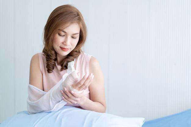 Azjatycka kobieta patrzeje jej rękę ranną od wypadku. pojęcie opieki zdrowotnej i wellness u osób dorosłych.