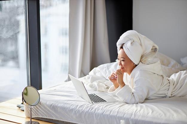 Azjatycka kobieta patrzy na ekran laptopa, rozmawia, uśmiecha się, prowadzi z kimś rozmowę online w domu na łóżku