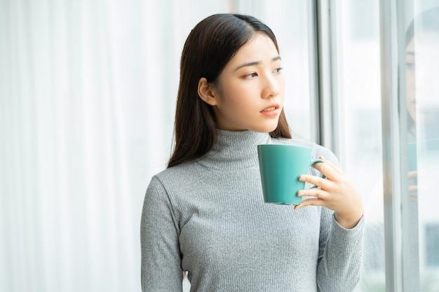 Azjatycka kobieta pijąca kawę przy oknie podczas przerwy