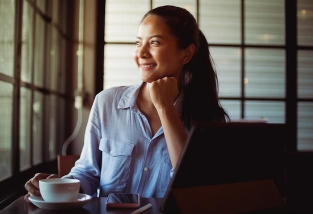 Azjatycka kobieta pije kawę i działanie z laptopem w kawiarni
