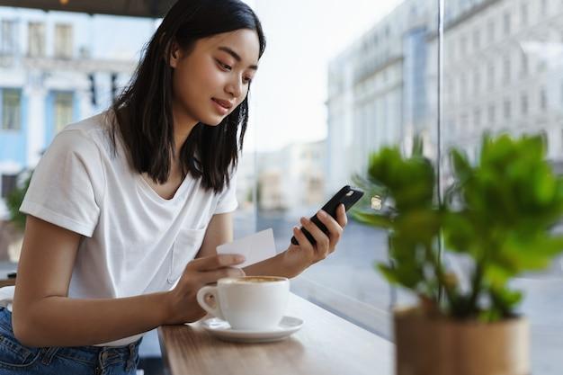Azjatycka kobieta pije kawę w kawiarni przy oknie i płaci za zakupy online.