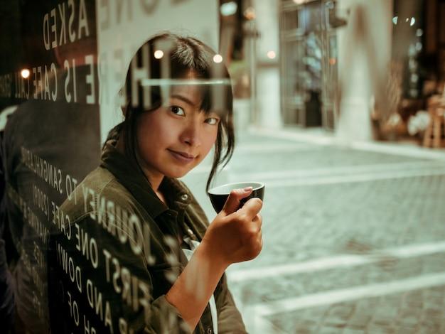 Azjatycka kobieta pije kawę w kawiarni