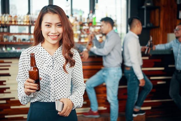 Azjatycka kobieta pije piwo przy pubem