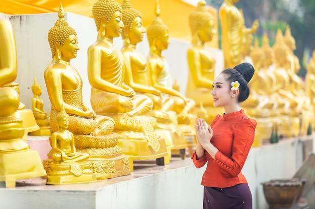 Azjatycka kobieta płacić szacunek buddha statua w thailand.