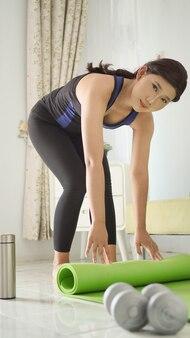 Azjatycka kobieta po jodze składa matę w domu