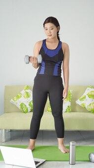 Azjatycka kobieta podnosi sztangę na pół ramienia stojąc w domu