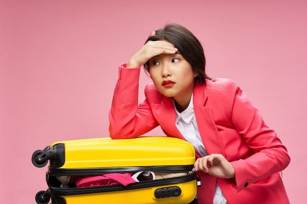 Azjatycka kobieta podróżuje z walizką w jej rękach, wakacje.