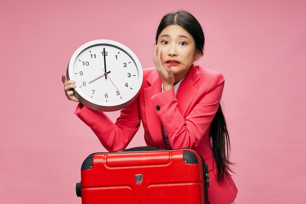 Azjatycka kobieta podróżuje z walizką w jej rękach
