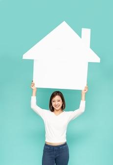 Azjatycka kobieta pokazująca i prezentująca biały dom na zielonym tle