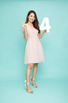 Azjatycka kobieta pokazująca numer 4 na zielonym tle