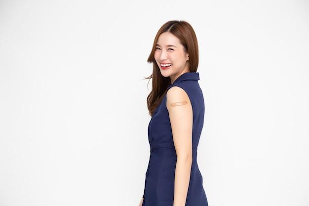 Azjatycka kobieta pokazująca ramię z gipsem zaszczepionego covid19 na białym tle