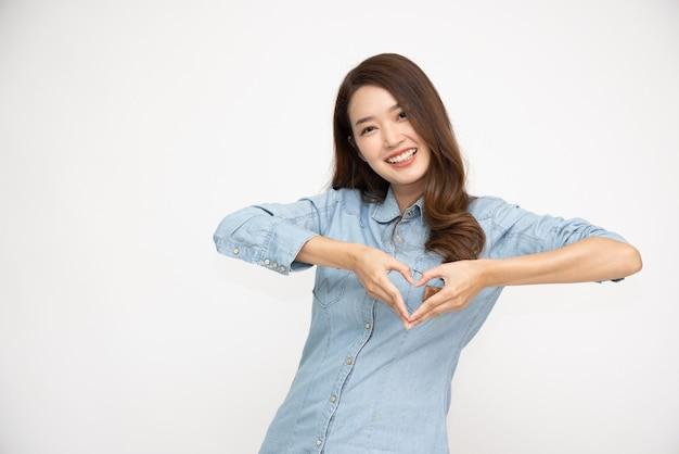 Azjatycka kobieta pokazująca znak serca na białym tle