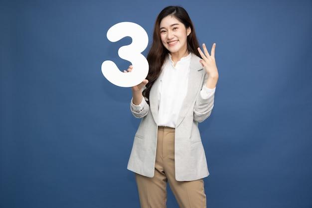 Azjatycka kobieta pokazuje numer trzy na białym tle na niebieskim tle