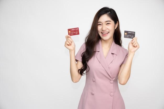 Azjatycka kobieta pokazuje, przedstawiając kartę kredytową do dokonywania płatności lub płacenia za biznes online.