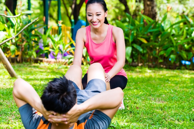 Azjatycka kobieta pomaga człowiekowi z ćwiczeniami rozciągającymi w parku na fitness