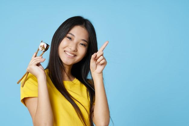 Azjatycka kobieta pozuje z karmowym portretem, suszi