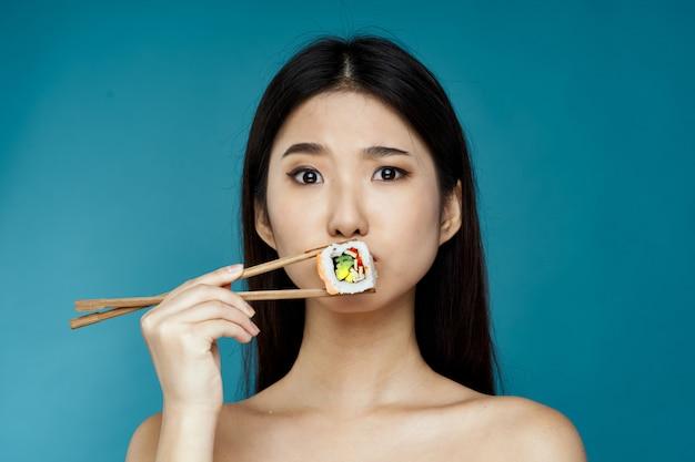 Azjatycka kobieta pozuje z suszi