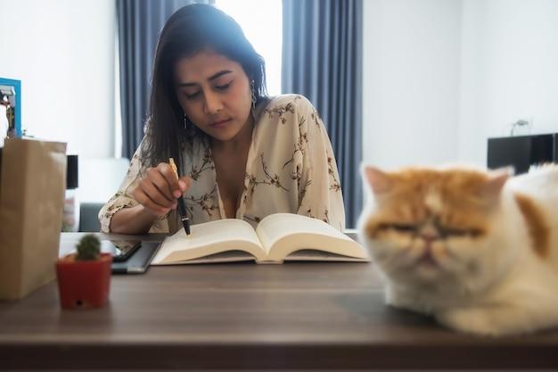 Azjatycka kobieta pracująca czyta książki i pracuje w domu z egzotycznym kotem krótkowłosym podczas pandemii covid-19 delta. zostań w domu, dystans społeczny, kwarantanna.