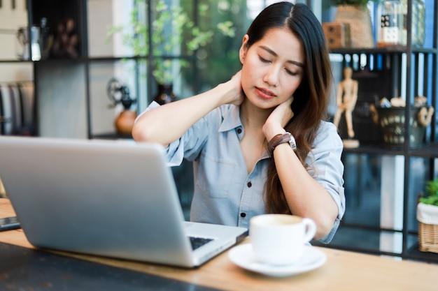Azjatycka kobieta pracuje kawę w kawiarni i pije z laptopu uśmiechem i szczęśliwą pracą