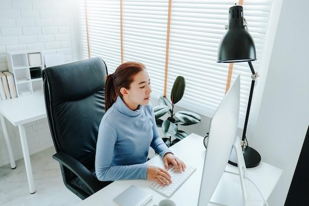 Azjatycka kobieta pracuje od domowego używa komputeru