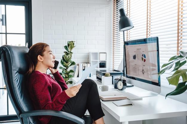 Azjatycka kobieta pracuje od domu używać komputer i pije kawę w jej sypialni