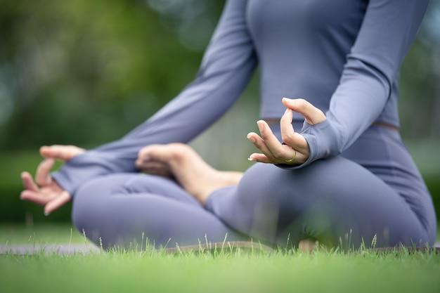 Azjatycka kobieta praktykuje jogę w miejskim ogrodzie