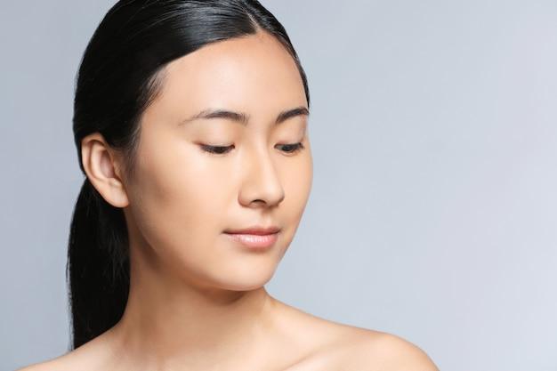 Azjatycka kobieta przed nałożeniem makijażu na szarym tle