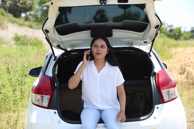 Azjatycka kobieta przy samochodzie za pomocą smartfona