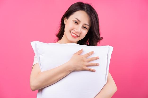 Azjatycka kobieta przytula poduszkę na różowo