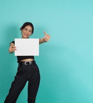 Azjatycka kobieta ręce trzyma pustą deskę i wskazując na miętowym zielonym tle. pusty papier.
