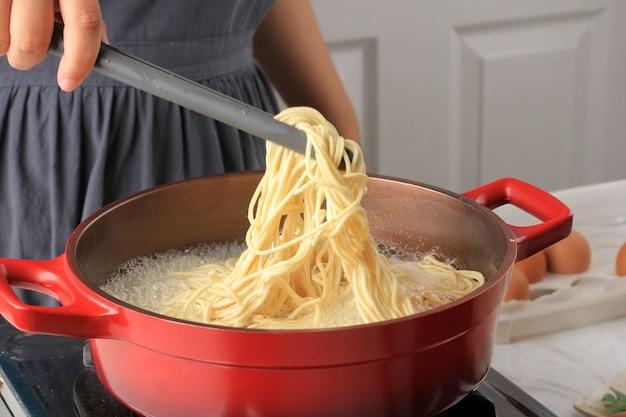 Azjatycka kobieta ręcznie gotowany azjatycki makaron (mie telur lub bakmi), proces gotowania w kuchni