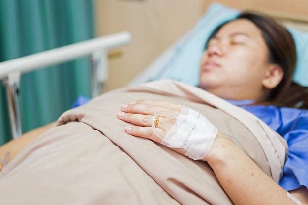 Azjatycka kobieta ręka jest na kroplówce otrzymywa zasolonego rozwiązanie, zastępująca terapia płynna strzał w lewym ar