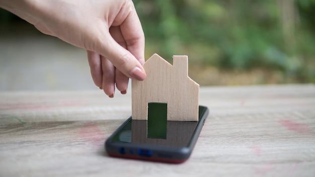 Azjatycka kobieta ręka trzyma drewniany dom, służy do kupowania nowej koncepcji domu.