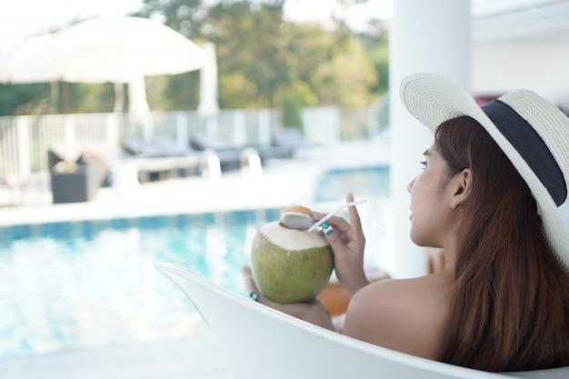 Azjatycka kobieta relaksuje przy pływackim basenem luksusowy kurort.