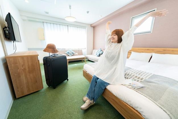 Azjatycka kobieta relaksuje się w prostym pokoju hotelowym