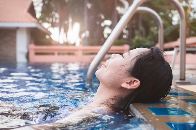 Azjatycka kobieta relaksuje w pływackim basenie z szczęściem i emocjami.