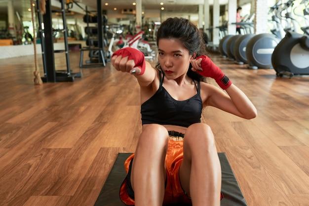 Azjatycka kobieta robi ćwiczeniom z jej rękami zawijać z czerwonym zespołem