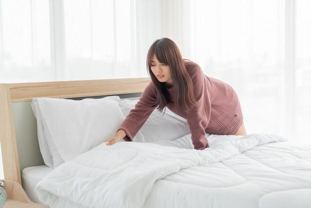 Azjatycka kobieta robi łóżku w pokoju z białym czystym prześcieradłem