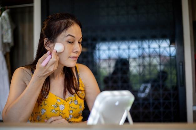Azjatycka kobieta robi makijaż w pokoju.