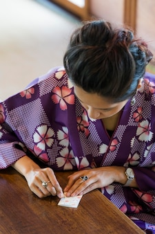 Azjatycka kobieta robi origami z japońskim papierem