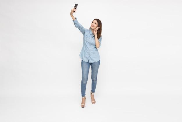 Azjatycka kobieta robi selfie przez telefon komórkowy na białym tle na białym tle