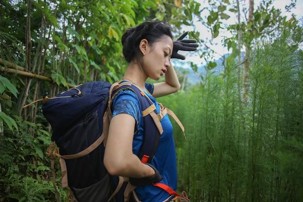 Azjatycka kobieta robi sobie przerwę podczas wędrówek
