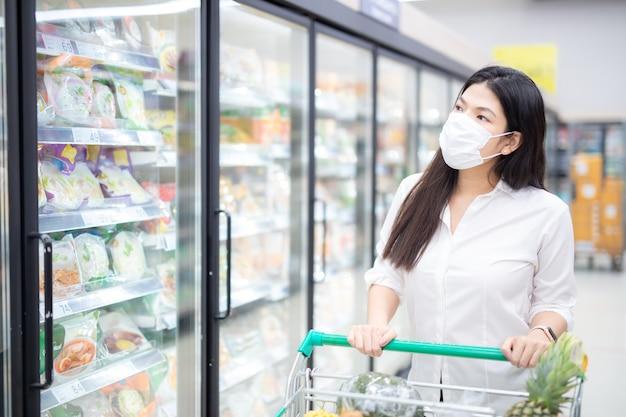 Azjatycka kobieta robi zakupy z maską, bezpiecznie kupuje artykuły spożywcze, środki bezpieczeństwa w supermarkecie.