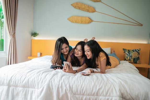 Azjatycka Kobieta Robi Zdjęcia Swoim Przyjaciołom Za Pomocą Telefonu, Spędzając Razem Czas W Sypialni I Selfie Premium Zdjęcia