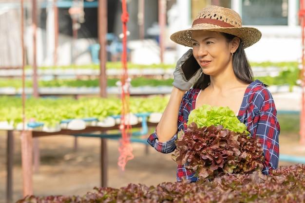 Azjatycka kobieta rolników pracujących przy użyciu telefonu komórkowego w uprawie hydroponicznej warzyw ze szczęścia. portret kobiety rolnik sprawdzanie jakości zielonej sałaty warzywnej z uśmiechem w gospodarstwie zielonym domu.