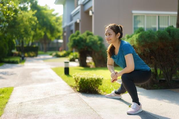Azjatycka kobieta rozciągająca się, aby się rozgrzać lub ochłodzić, przed lub po ćwiczeniach, w pobliżu drzwi wejściowych w sąsiedztwie, aby zapewnić codzienne zdrowie i dobre samopoczucie, zarówno fizyczne, jak i psychiczne.