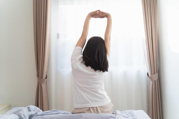 Azjatycka kobieta rozciągająca się w sypialni po przebudzeniu, widok z tyłu
