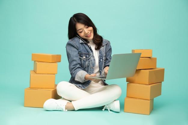 Azjatycka kobieta rozmawia przez telefon i siedzi na podłodze ze skrzynką na paczki i laptopem